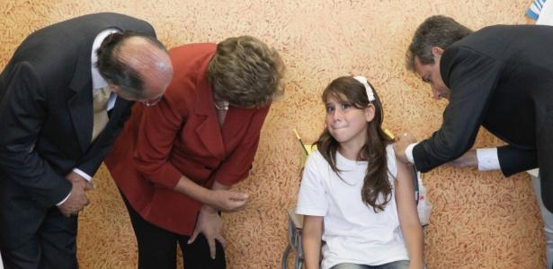 Ministro da Saúde vacina menina enquanto é observado pela presidente Dilma e pelo governador de SP