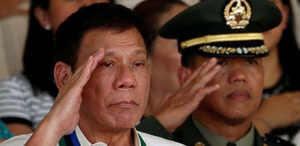 O presidente das Filipinas, Rodrigo Duterte, bate continência ao lado de oficial no Campo Aguinaldo, em Quezon City, Manila